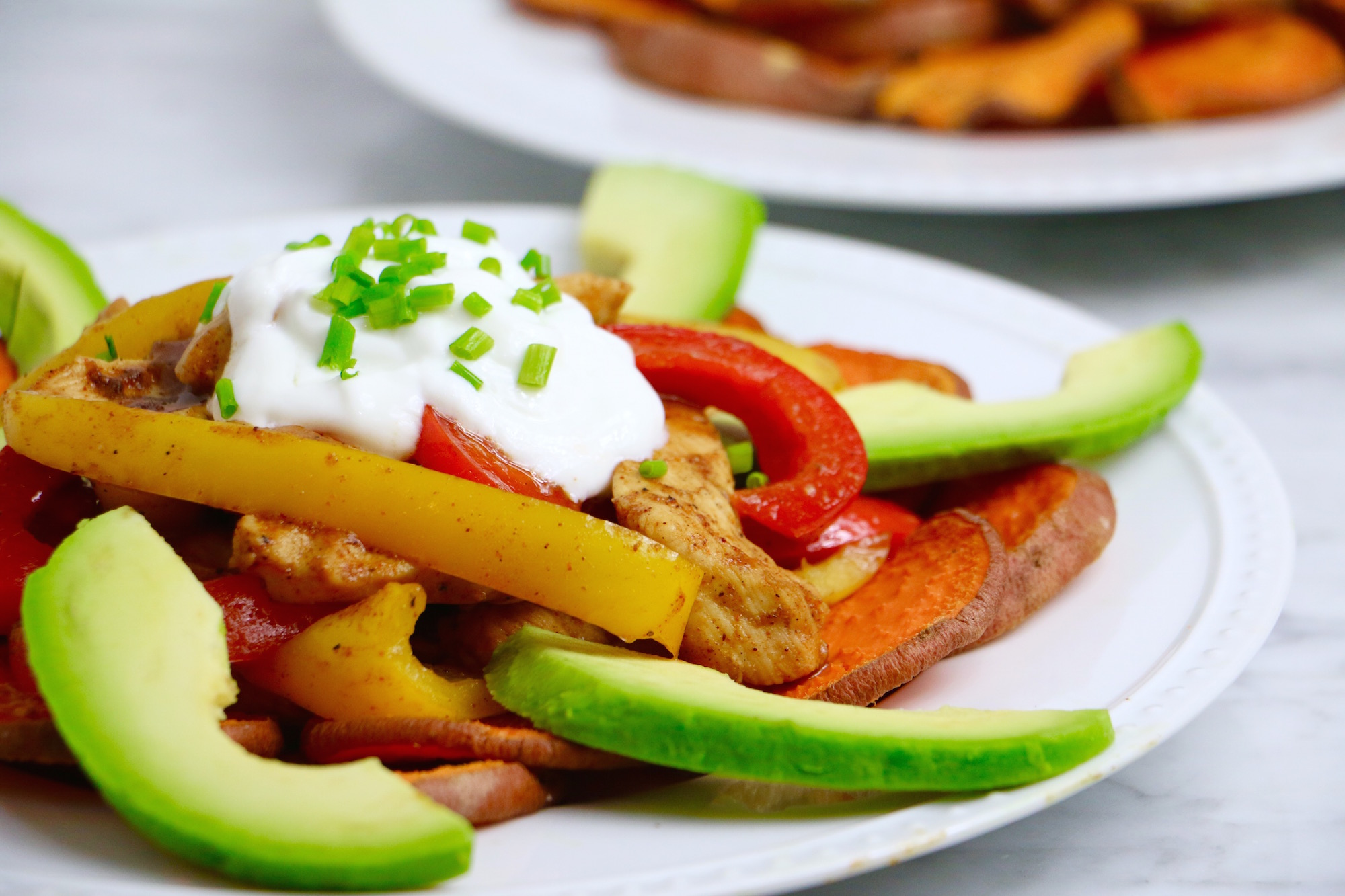 Healthy Chicken Fajita Nachos made with Baked Sweet Potato Chips and topped with organic chicken, red and yellow bell peppers, avocado, and greek yogurt. Gluten-free + can be made vegan by swapping beans. Takes 30 minutes to make!